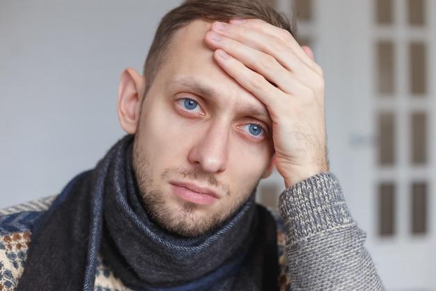 Mal sentimiento y frustración. el hombre enfermo tiene temperatura alta.