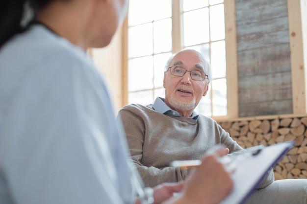 Mala salud. doctor que lleva el portapapeles mientras toma notas y conversa con un hombre mayor feliz y guapo