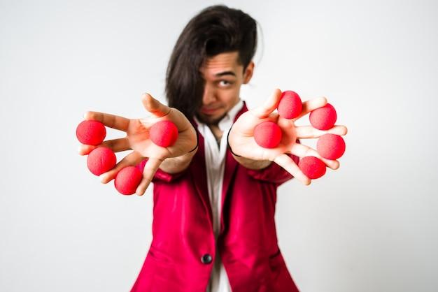 Malabarista colocando bolas rojas entre sus dedos para divertidos y económicos trucos.