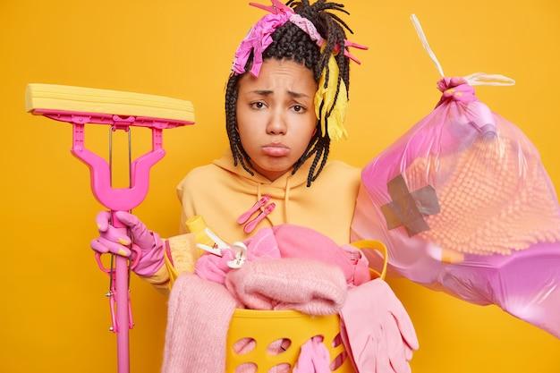 Malestar aburrido joven afroamericana con rastas recoge basura en una bolsa de basura