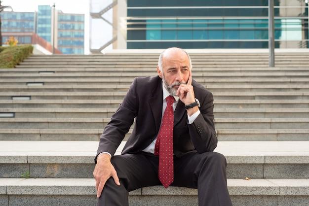 Malestar empresario sentado en pasos
