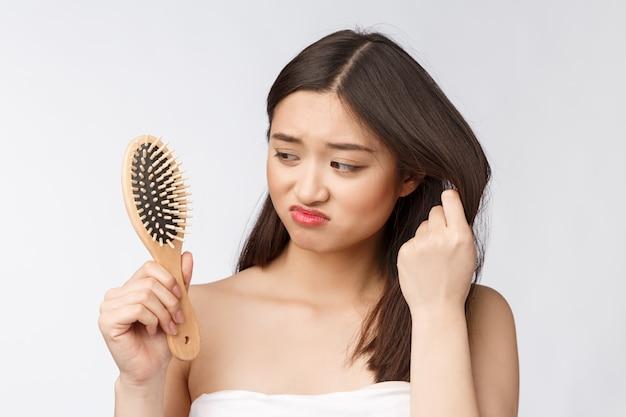 Malestar estresada joven asiática con cabello seco dañado en manos sobre blanco aislado