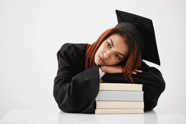 Malestar graduado africano acostado en libros pensando sentado. copia espacio