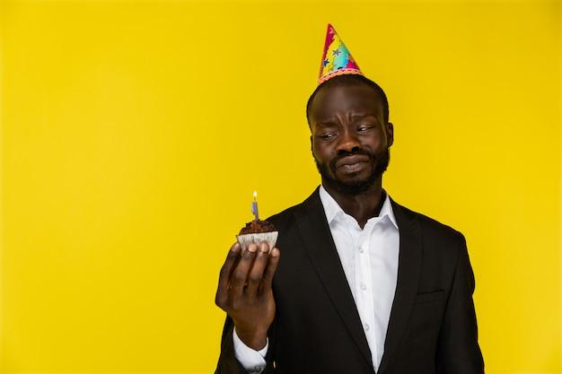 Malestar joven afroamericano en traje negro y sombrero de cumpleaños con velas encendidas