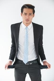 Malestar joven empresario mostrando los bolsillos vacíos
