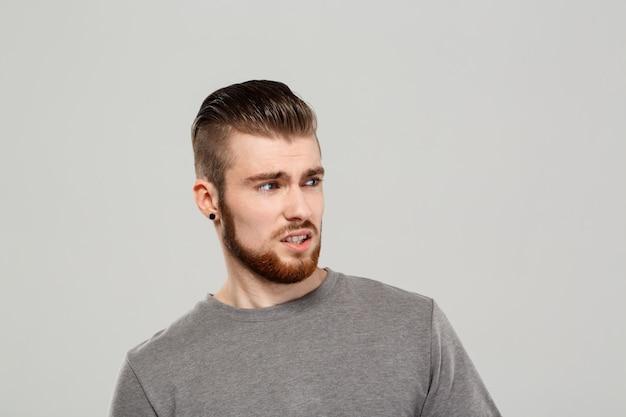 Malestar joven guapo posando sobre pared gris.