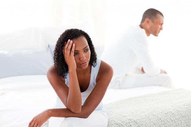 Malestar joven pareja sentada en la cama por separado