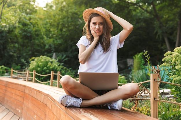 Malestar joven sentada con ordenador portátil en el parque al aire libre