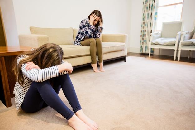 Malestar madre e hija sentada en la sala