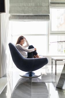 Malestar mujer llorar cubriéndose la cara con la mano. concepto de joven depresión, estrés y problemas, dolor, mujer deprimida sentada en una silla de cerca con las manos