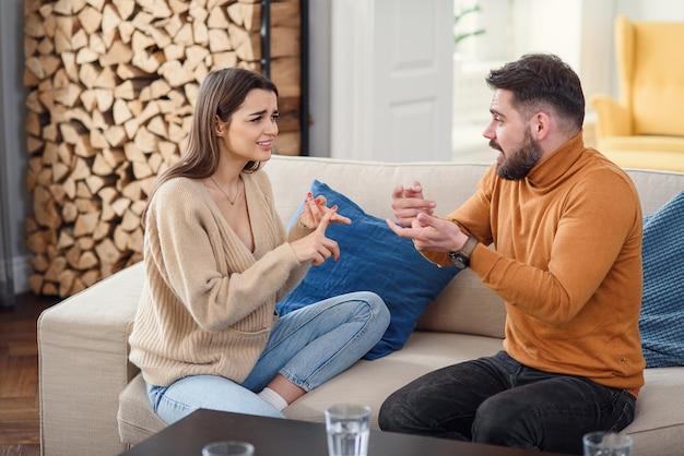 Malestar pareja en casa. el hombre hermoso y la mujer joven hermosa están teniendo pelea. sentados juntos en el sofá. problemas familiares.