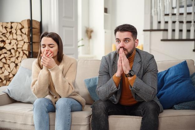 Malestar pareja en casa. el hombre hermoso y la mujer joven hermosa están teniendo pelea. sentados en el sofá juntos. problemas familiares.