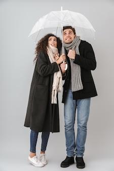 Malestar pareja congelada vistiendo ropa autimn de pie bajo un paraguas aislado sobre pared gris