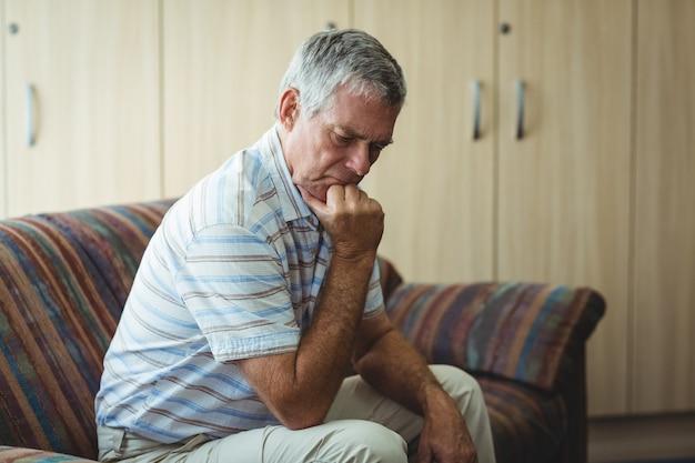 Malestar senior hombre sentado en la sala de estar