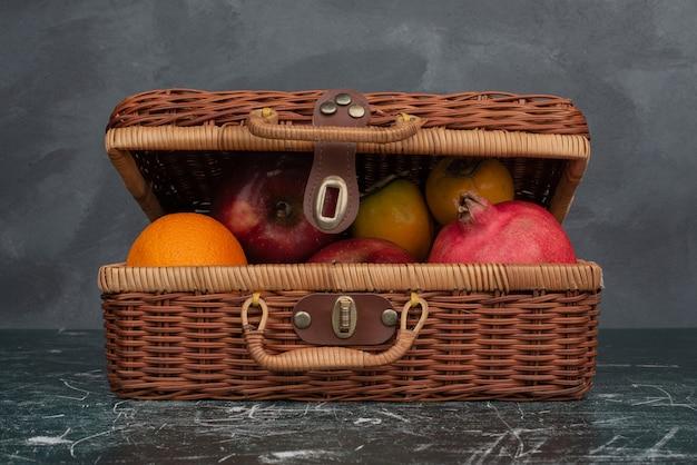 Maleta abierta llena de frutas sobre mesa de mármol.