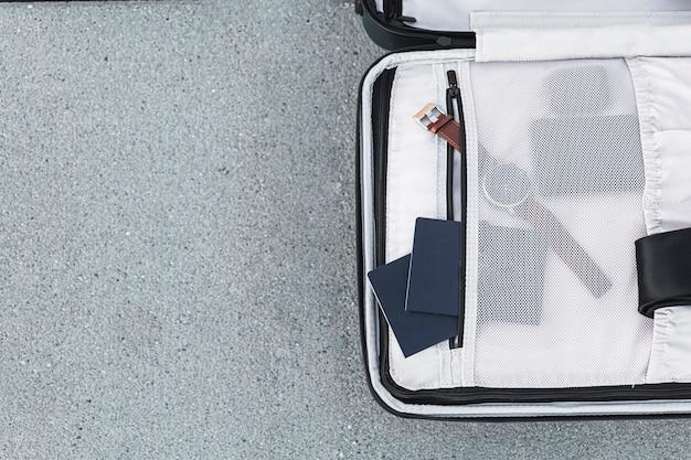 Maleta abierta con pasaportes y reloj.