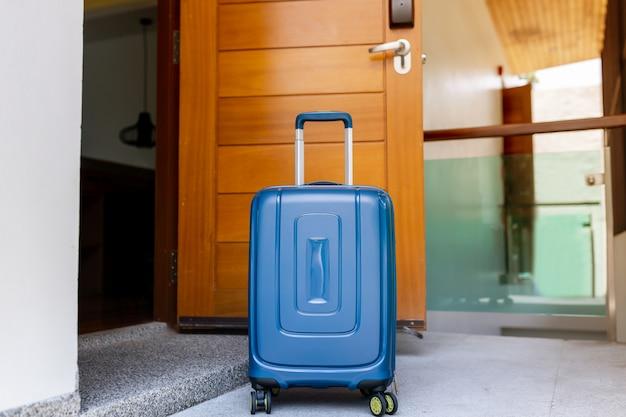 Maleta azul en habitación de hotel con detalles de madera marrón. copia espacio