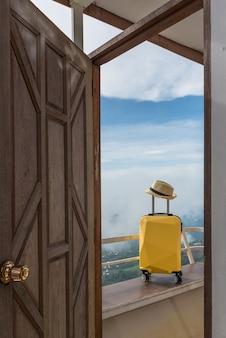 Maleta, bolsa de viaje con sombrero en el hotel o alojamiento con hermosos paisajes.