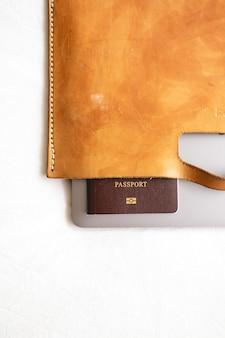 Maleta de cuero con pasaporte y portátil en concepto de negocio de viajes.
