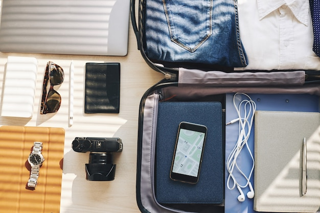 Maleta, dispositivos electrónicos y objetos personales organizados para viajes de negocios.