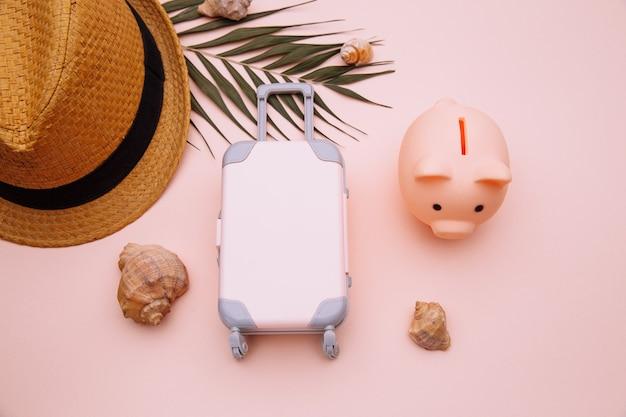 Maleta de equipaje de viaje con alcancía en mesa rosa con primer plano de accesorios.