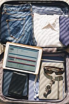 Maleta lista para viaje de negocios y eticket en pantalla de tableta
