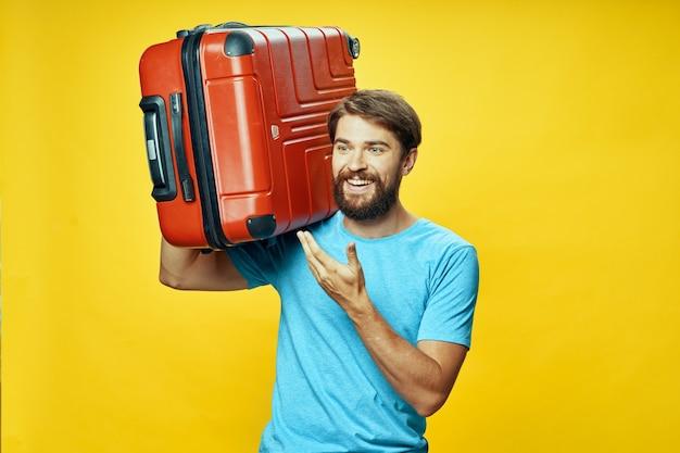 Maleta en la mano de un viajero feliz riendo fondo amarillo