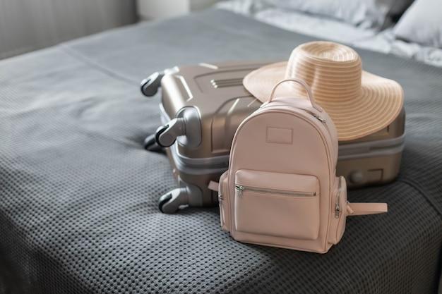 Maleta moderna llena de cosas, bolso de mano y sombrero de paja, caja de equipaje, embalaje, preparándose para viajar