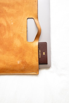 Maleta de piel con pasaporte y portátil.