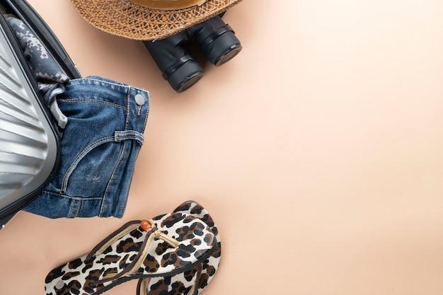 Maleta plana de color gris con binoculares, gorro, jeans y sandalias. concepto de viaje