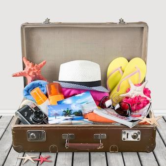 Maleta retro con objetos de viaje en el escritorio