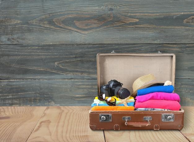 Maleta retro con objetos de viaje en el fondo