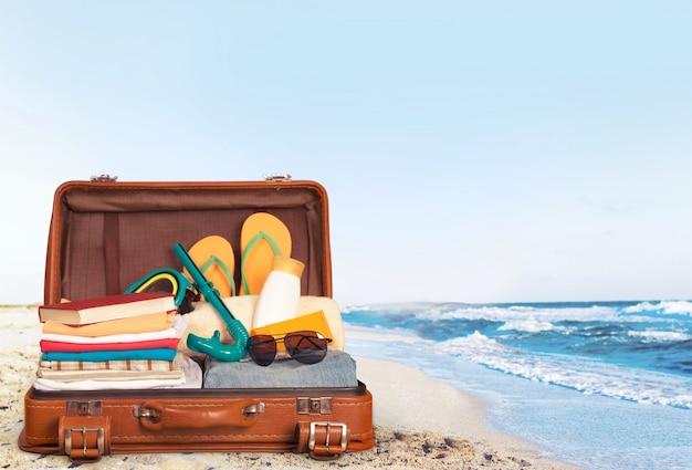 Maleta retro con objetos de viaje sobre tabla de madera sobre fondo natural