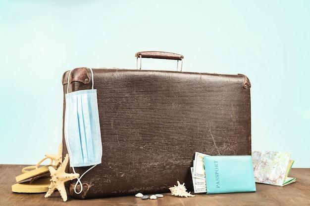 Maleta retro con pasaporte, accesorios de viaje y máscara médica.