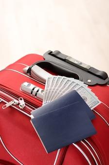 Maleta roja, pasaportes y dinero sobre un piso de madera en una habitación vacía