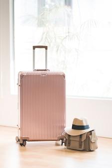 Maleta rosa y bolso y gorro para viajar.