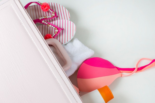 Desde la maleta rosa puedes ver cosas para la playa: crema solar, traje de baño, toalla, zapatillas.