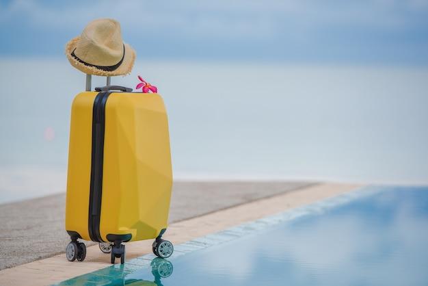 Maleta y sombrero de viaje en el hermoso paisaje marino con reflejo