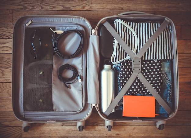 Maleta de viaje abierta llena de ropa aislada sobre superficie de madera
