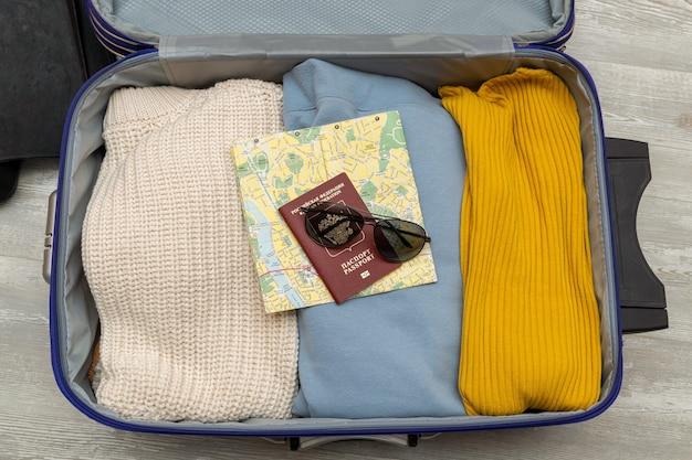 Maleta de viaje con ropa de colores apilados