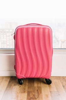 Maleta de viaje rosa de plástico con ruedas sobre suelo de madera.