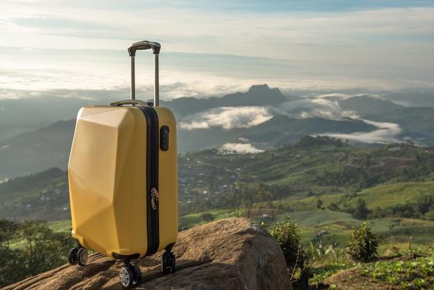 Maleta de viaje sobre la naturaleza del bello paisaje de montaña y la niebla.