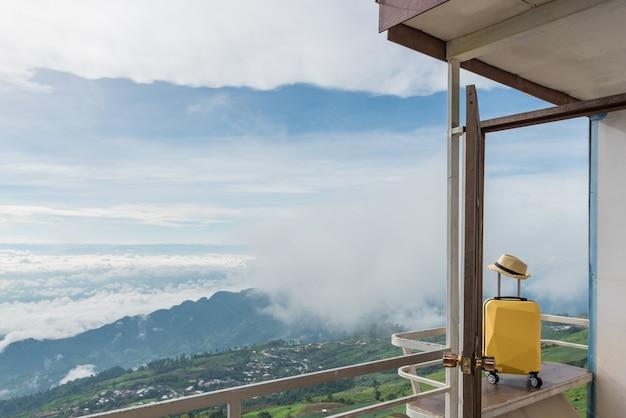 Maleta de viaje con sombrero sobre la naturaleza del hermoso paisaje de montaña y la niebla