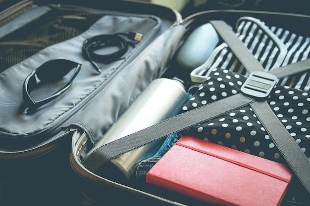 Maleta de viaje vintage abierta llena de ropa