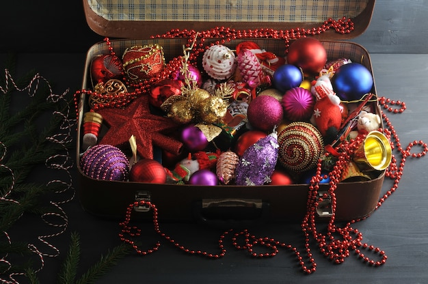 Maleta vintage con decoraciones festivas de navidad para el árbol de navidad.