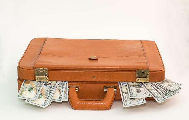 Maletín de cuero con dinero saliendo de los costados.