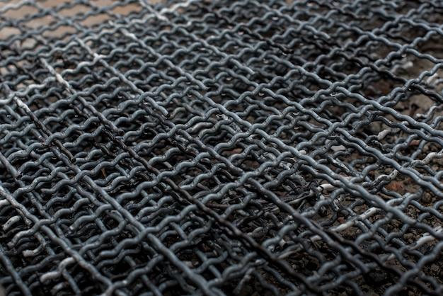 Malla para una valla de metal se encuentra en el suelo en primer plano. producción.