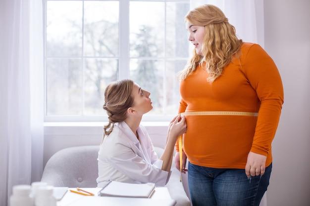 Malos resultados. médico profesional disgustado hablando con una mujer gorda y midiéndola