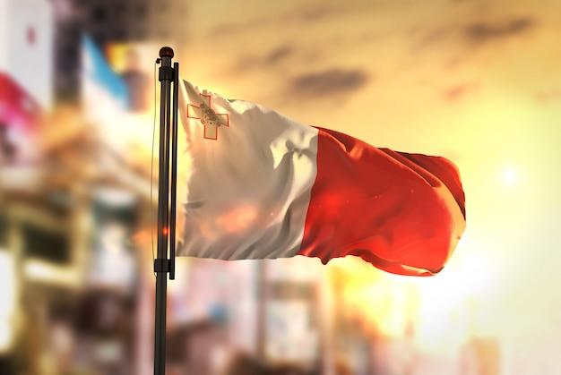 Malta bandera contra la ciudad borrosa de fondo a la salida del sol