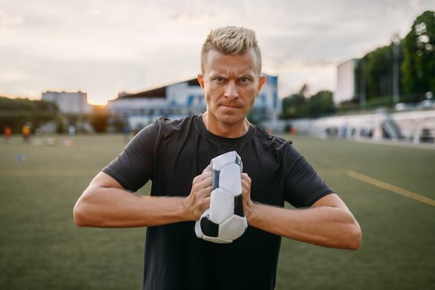 El malvado jugador de fútbol arrugó la pelota en el campo. futbolista en el estadio al aire libre, entrenamiento antes del juego, entrenamiento de fútbol